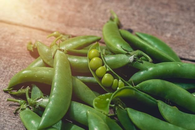 Guisantes verdes o frijoles en la mesa de madera