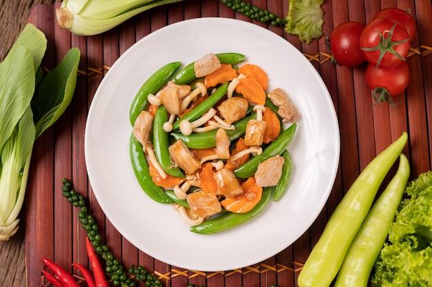 Los guisantes verdes salteados con setas de cerdo y zanahorias están en una placa blanca.
