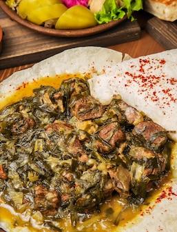 Guiso de carne, turshu govurma con cebolla, hierbas verdes, zanahorias en salsa de caldo.