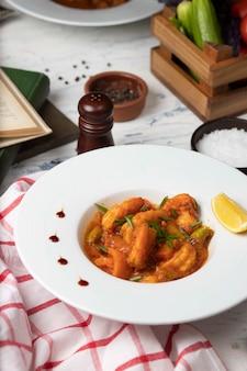 Guiso de patas de pollo en salsa de tomate en un tazón blanco con verduras y limón.