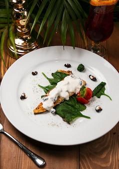 Guiso de pescado en salsa cremosa, tomate, perejil en el plato, cuchillo, tenedor