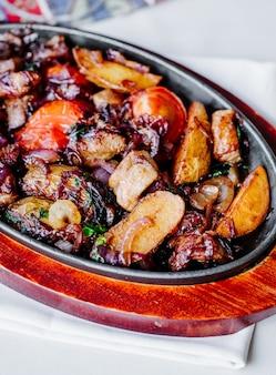 Guiso de verduras y carne dentro de una sartén negra.