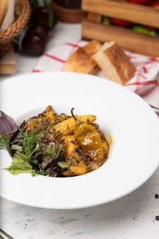 Guiso de verduras con carne, trozos de maíz, ají y vegetales, basílicos, perejil en plato blanco.