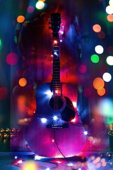 Guitarra acústica clásica en luces navideñas en memoria de la música