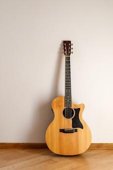 Guitarra acústica contra la pared.