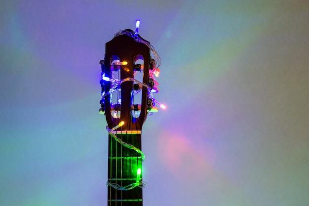 Guitarra acústica envuelta por una colorida guirnalda. regalo musical de navidad y año nuevo como fondo