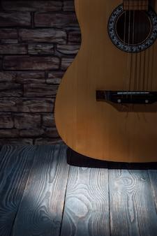 Guitarra acústica en el fondo de una pared de ladrillo con un haz de luz en una mesa de madera.