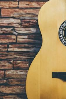 Guitarra acústica en un fondo de la pared de ladrillo.