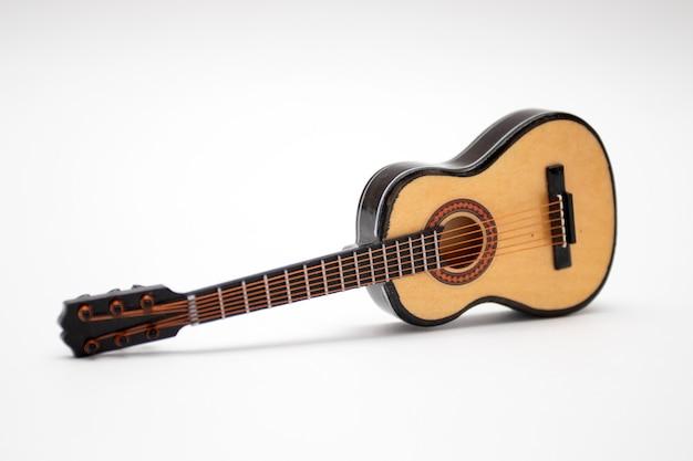 Guitarra acústica de juguete modelo pequeño sobre fondo blanco.