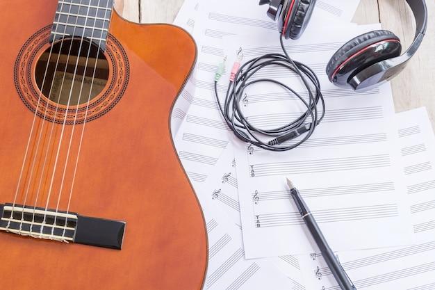 Guitarra acústica, partituras, auriculares grandes, pluma estilográfica en mesa de madera