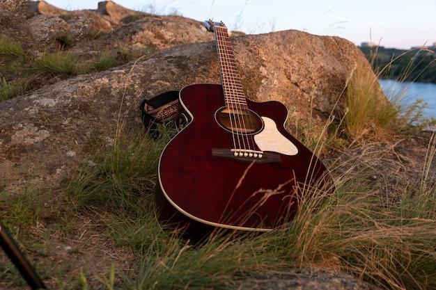 Guitarra acústica en la roca. guitarra al atardecer, concepto de fondo de música. instrumento acústico