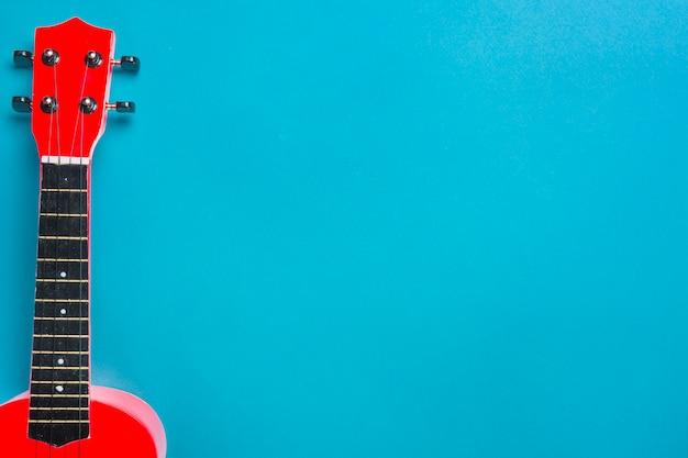 Guitarra acústica roja sobre fondo azul