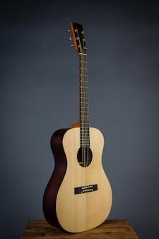 Guitarra acústica en una silla en pared negra.