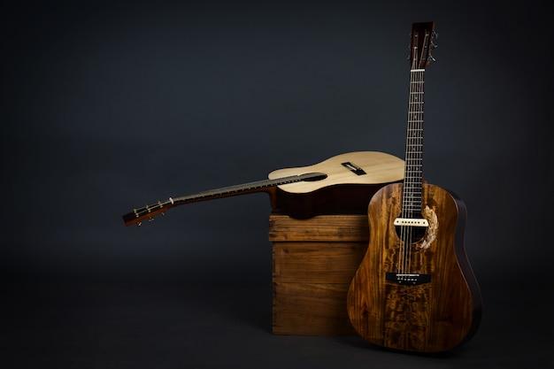 Guitarra acústica en una silla y primer plano guitarra marrón en pared negra.