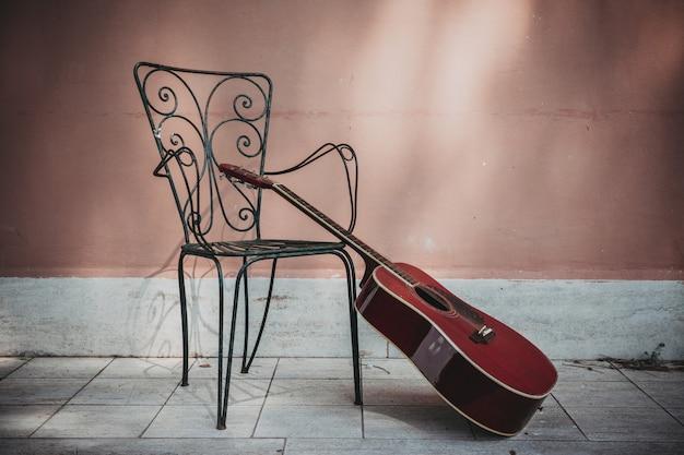 Guitarra acústica situada frente a la casa con silla vacía, estilo vintage