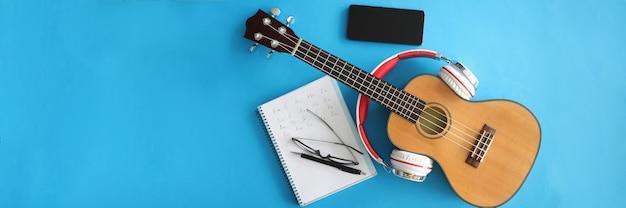 Guitarra con auriculares, smartphones y portátil sobre fondo azul.