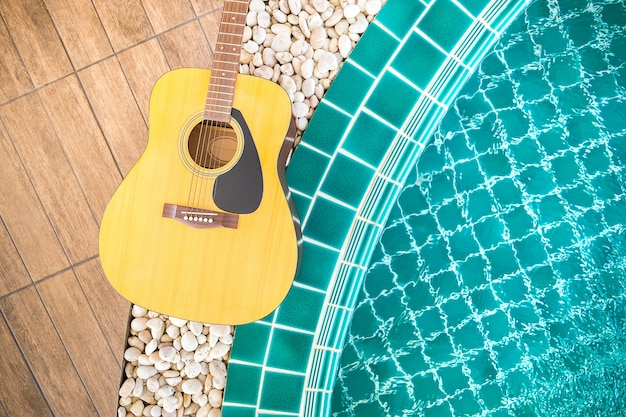 Guitarra en camino de madera junto a la piscina.
