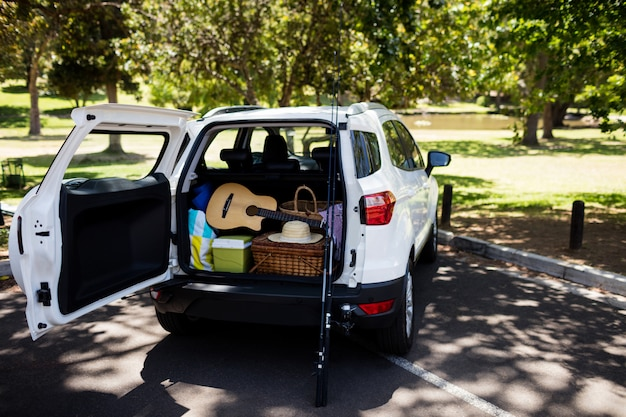 Guitarra, caña de pescar, canasta de picnic en el baúl del auto