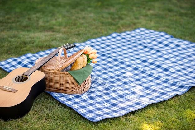 Guitarra y una cesta de picnic en una manta.
