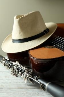 Guitarra clásica, clarinete y sombrero de mesa de madera blanca