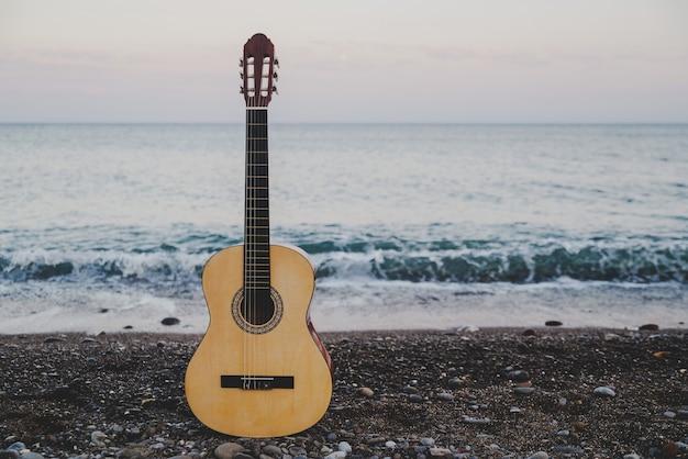 Guitarra clásica en la playa con vistas al mar.