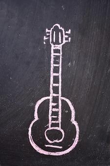 Guitarra dibujada en una pizarra negra