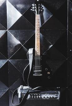 Guitarra eléctrica y amplificador clásico sobre un fondo oscuro.