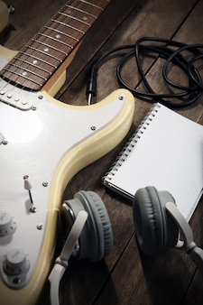 Guitarra eléctrica con auriculares y micrófono sobre fondo de madera