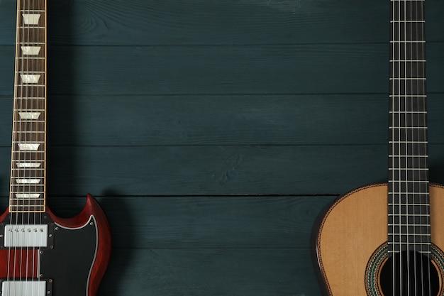 Guitarra eléctrica y clásica en mesa de madera.