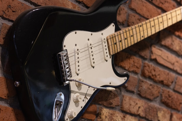 Guitarra eléctrica en la pared de ladrillo concepto de decoración de instrumentos musicales