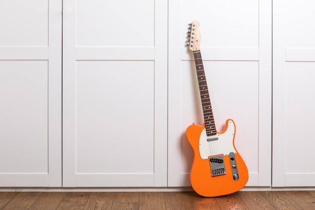 Guitarra eléctrica de pie cerca de la pared blanca en la sala