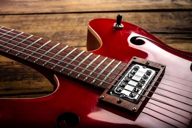 Guitarra eléctrica roja sobre suelo de madera