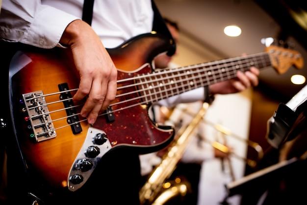 Guitarra electrónica en manos de un hombre vestido con una camisa blanca.