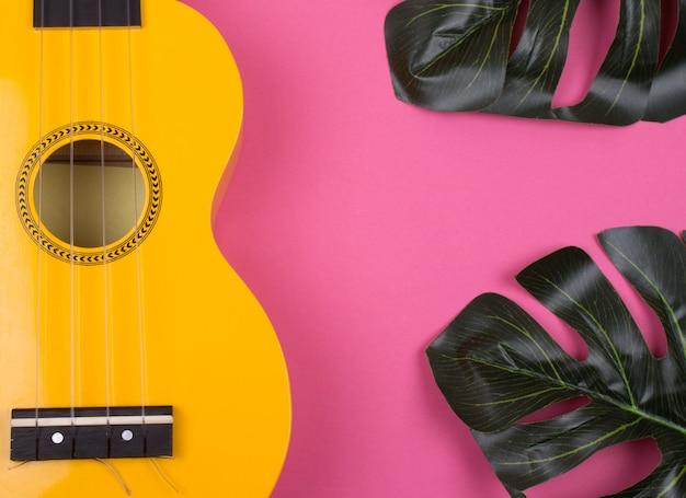 Guitarra ukelele amarilla y hojas de monstera