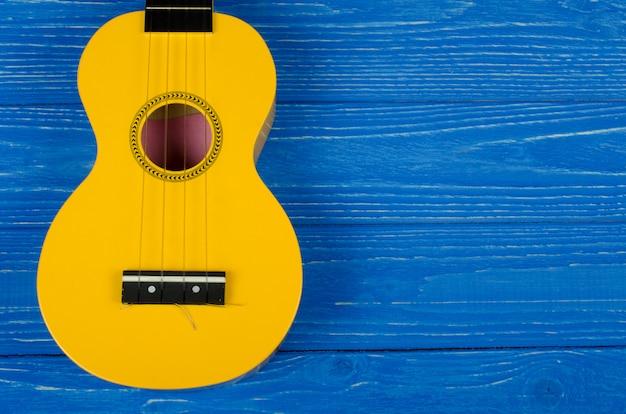 Guitarra ukelele amarilla sobre un fondo azul.