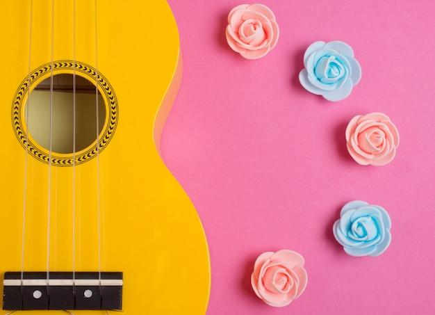 Guitarra ukelele y capullos de rosa hechos a mano sobre un fondo rosa