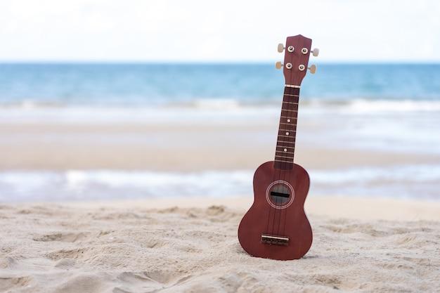 Guitarra ukelele puesta en la playa de arena. vista al mar durante el día con cielo azul.
