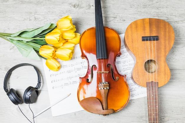 Guitarra; violín; tulipanes; auricular; lápiz en nota musical sobre la mesa