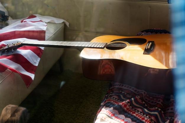 Guitarra y bandera americana en van rear seat road trip travel journey