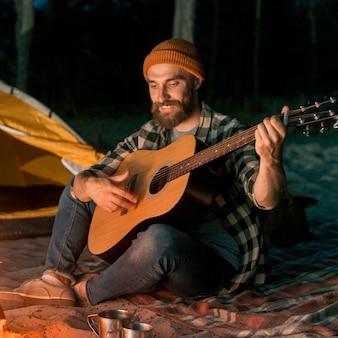 Guitarrista acampando y cantando junto a una hoguera.