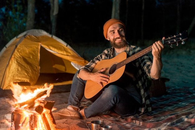 Guitarrista acampando en la noche junto a una fogata.