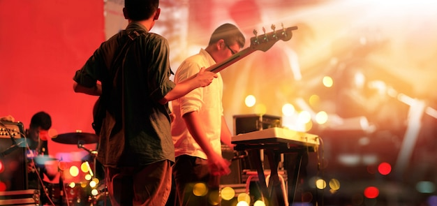 Guitarrista y banda en el escenario para el fondo.