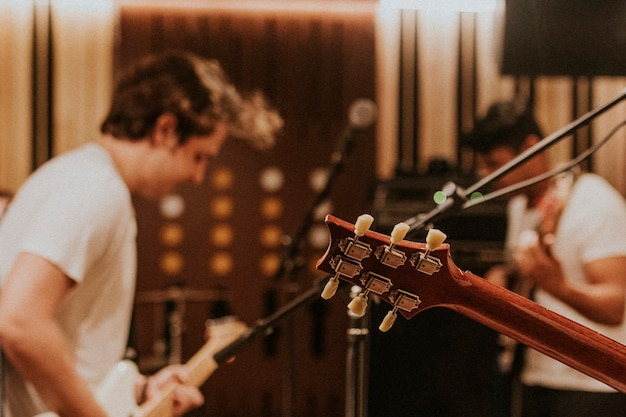 Guitarrista de la banda de música realizando repetición en el estudio de grabación