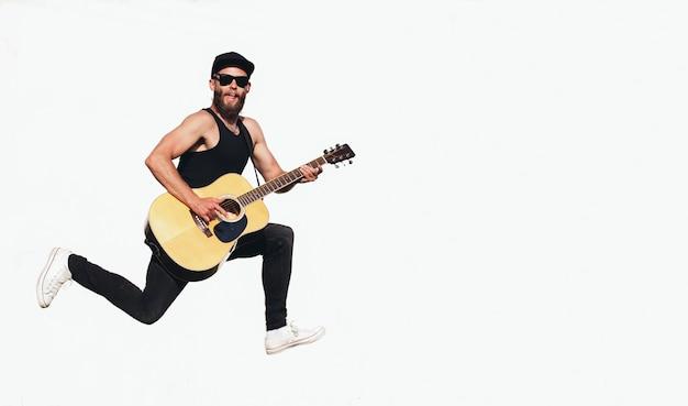 Guitarrista cantando afuera. guitarrista hipster con barba y ropa negra