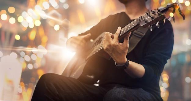 Guitarrista en el escenario y canta en un concierto.