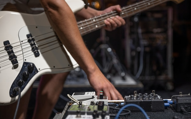 Un guitarrista masculino configurando efectos de procesamiento de audio de guitarra en el escenario.