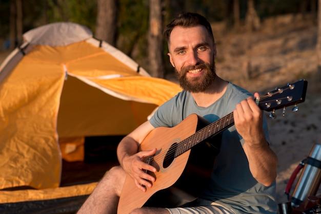 Guitarrista mirando a la cámara junto a la carpa