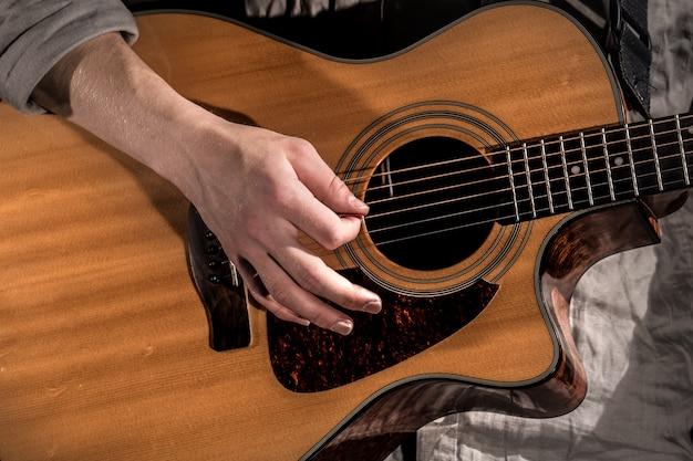 Guitarrista, música. joven toca una guitarra acústica en un negro aislado