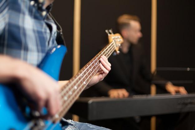 Guitarrista con pianista en el fondo
