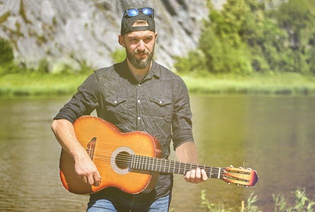 El guitarrista toca la guitarra, de pie contra el fondo del río salvaje en un día soleado de verano.